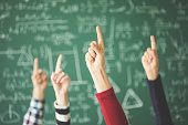 istock Students raised up fingers green chalk board in classroom 944039966