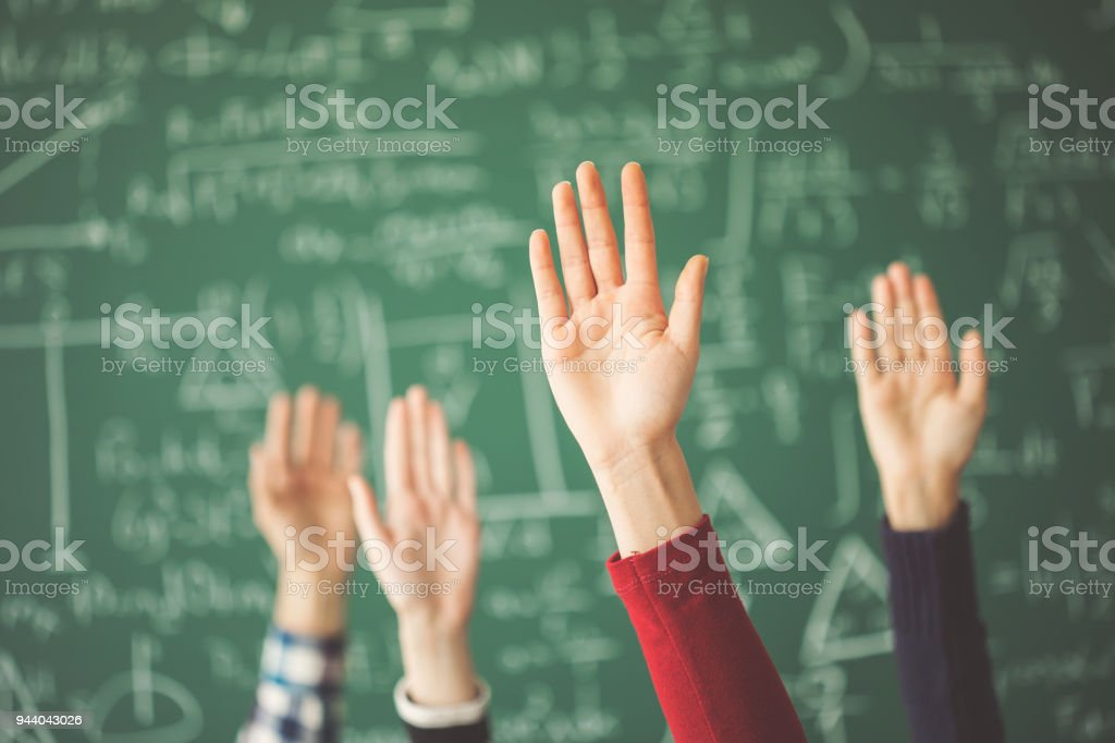 Estudiantes levantados las manos pizarra verde en aula foto de stock libre de derechos