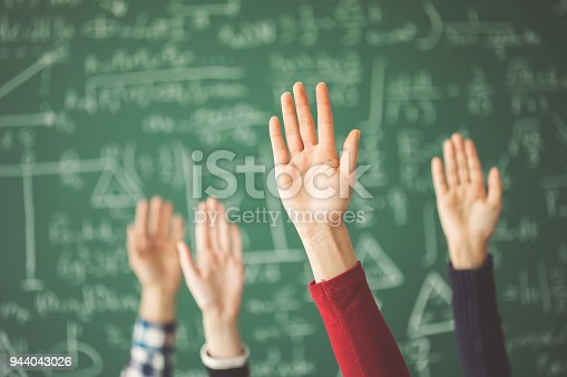 istock Students raised up hands green chalk board in classroom 944043026