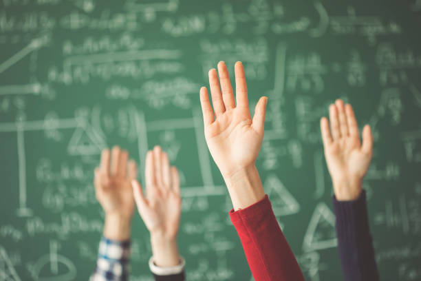Students raised up hands green chalk board in classroom - foto stock