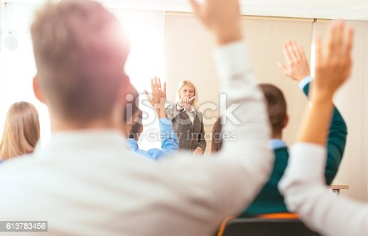 933450738 istock photo Students raising hands during class 613783456