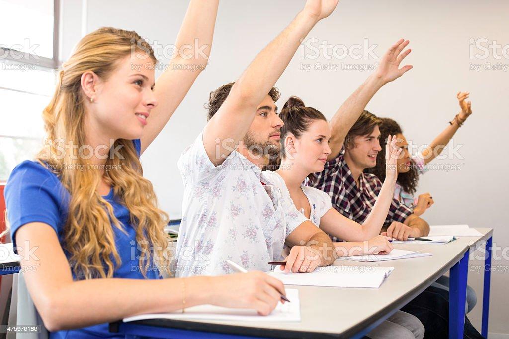 Students raising hands in classroom stock photo