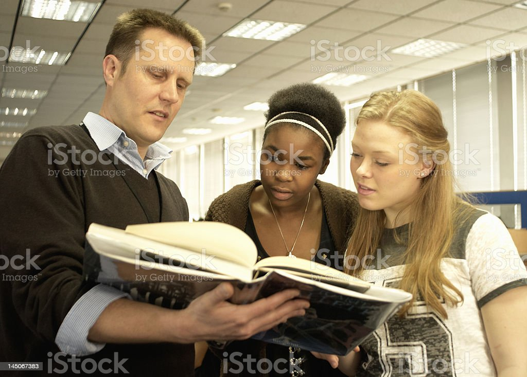 Students reading with teacher in library stock photo