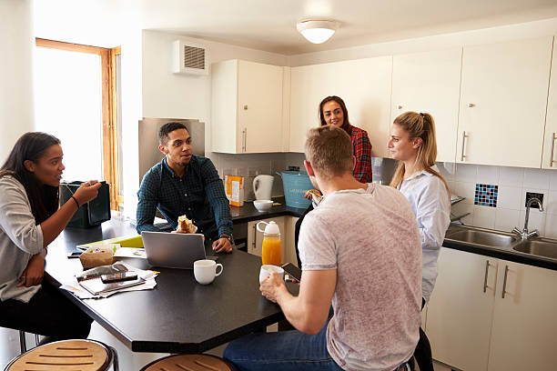 students relaxing in kitchen of shared accommodation - studentenküche stock-fotos und bilder