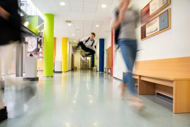 Students running through the school hallway.