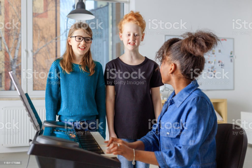 Students singing while teacher playing piano Female teacher playing piano while girls singing together. Pre-adolescent students are practicing during music lesson. They are learning in conservatory. 10-11 Years Stock Photo