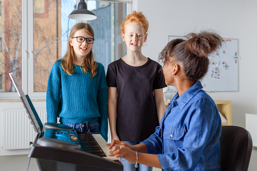 Students Singing While Teacher Playing Piano Stock Photo - Download Image Now