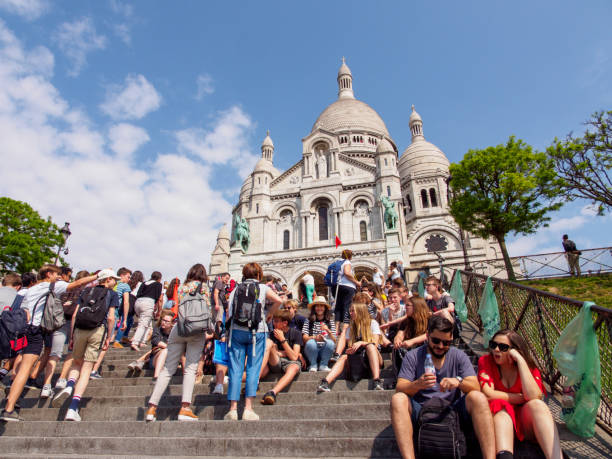 Students sit in front of Sacre Coeur, Montmarte, Paris, France stock photo