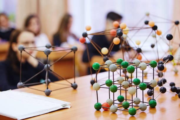 schüler im klassenzimmer sitzen und hören sie einen vortrag in der wissenschaft. molekulare pädagogische modell aus kunststoff. soft-fokus-hintergrund-bild - physik stock-fotos und bilder