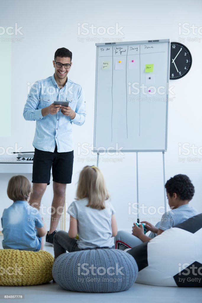 Students sit on colorful pouf stock photo