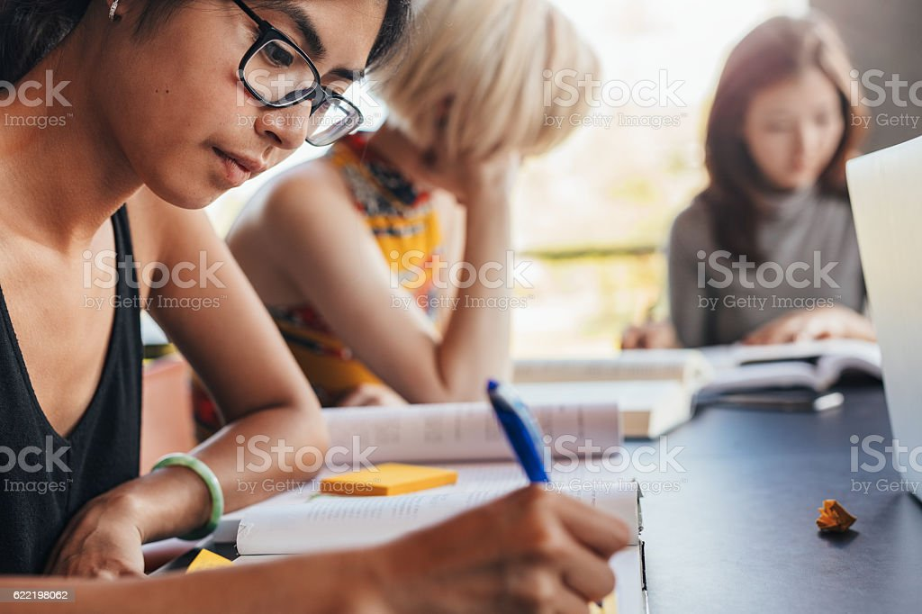 Students sitting at library with books and studying stock photo