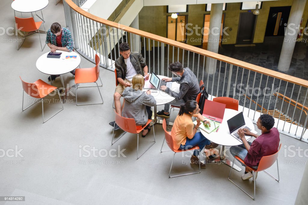 Students sitting at tables using laptops and meeting friends stock photo