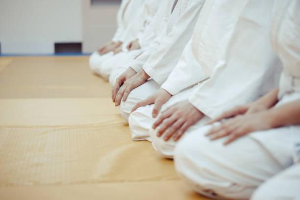 estudiantes sentados en un kimono en el gimnasio - artes marciales fotografías e imágenes de stock