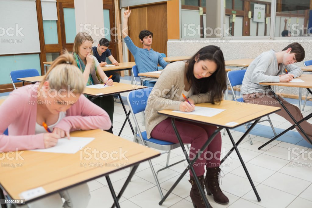 Students sitting in exam hall while student is raising hand to ask...