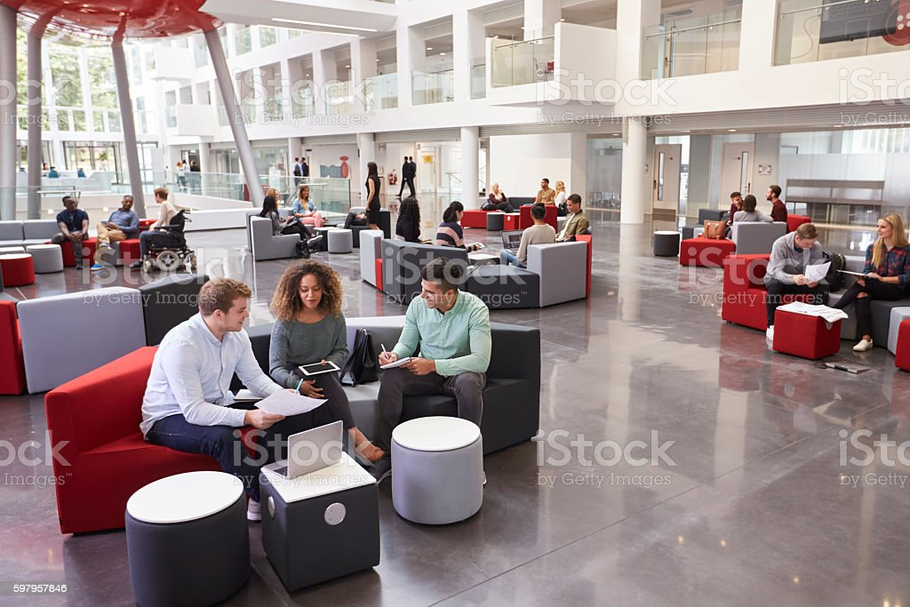 Students sitting in university atrium, three in foreground