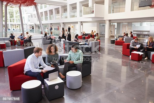 istock Students sitting in university atrium, three in foreground 597957846