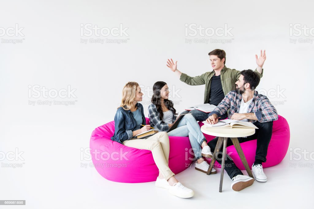 students sitting on beanbag chairs and studying in studio on white stock photo