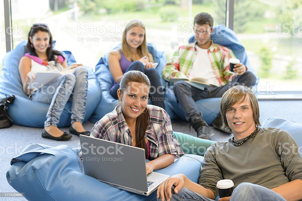 Students sitting on beanbags in study room stock photo