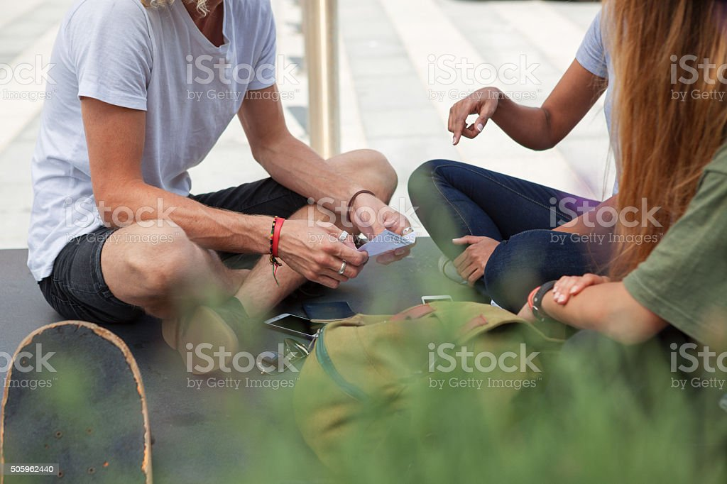 students sitting on ground outside stock photo