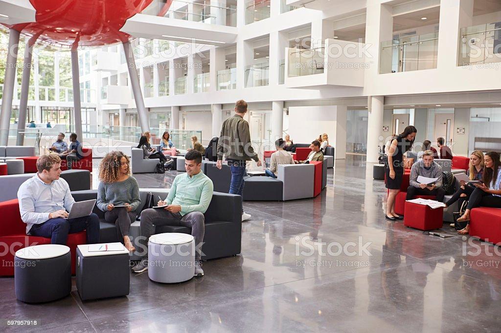 Students socialising in the lobby of modern university stock photo