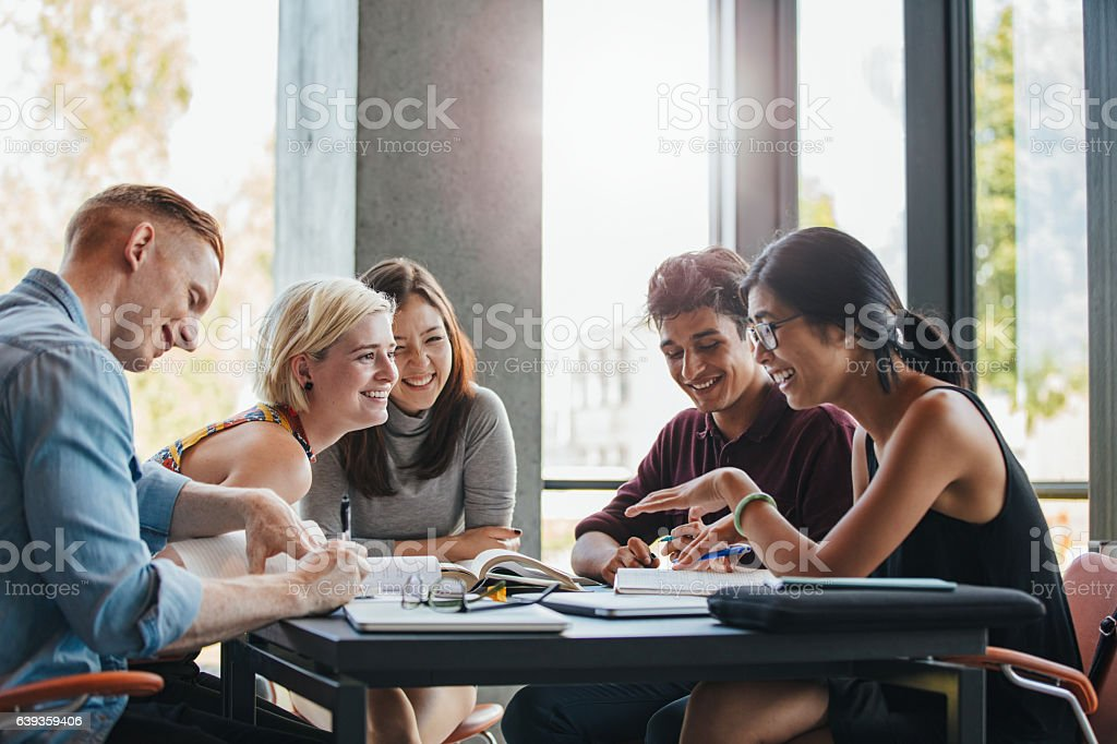 Students studying in college library - foto stock