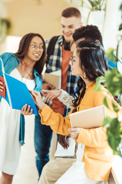 students talking about homework young students talking about homework together in college corridor college fair stock pictures, royalty-free photos & images