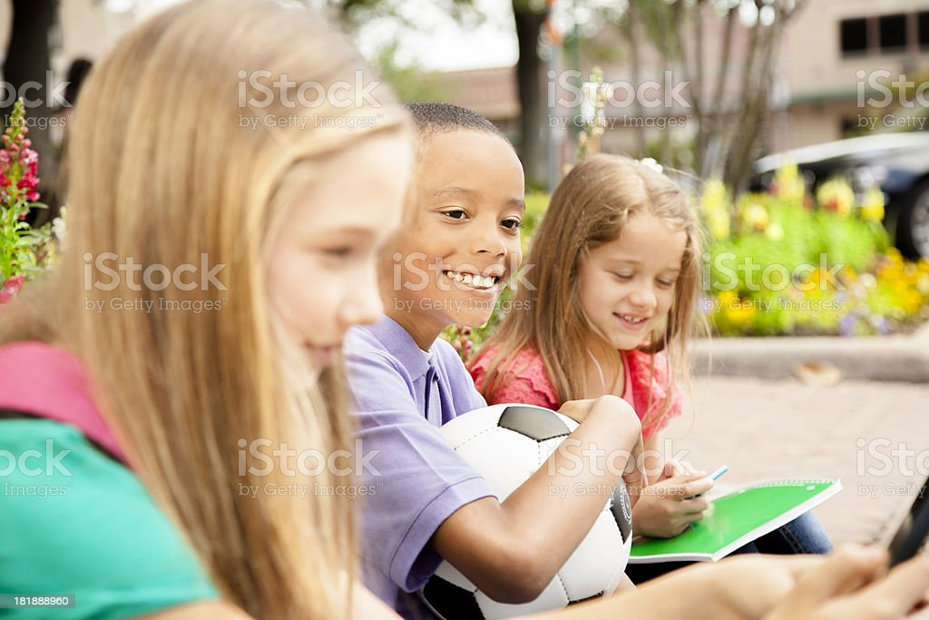 Students:  Three elementary mixed ethnic children waiting for parents royalty-free stock photo