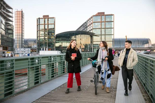 Studenten zusammen über eine Fußgängerbrücke mit dem Fahrrad in Berlin, Deutschland – Foto