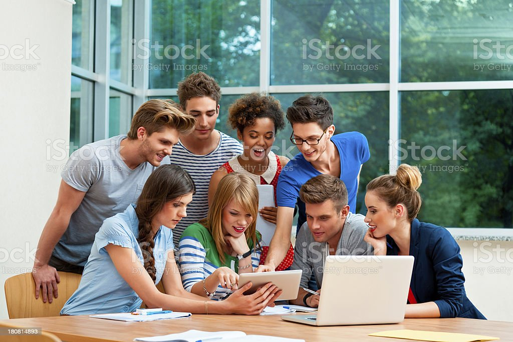 Students using a digital tablet Large group of happy university students gathering around a digital tablet. 20-24 Years Stock Photo
