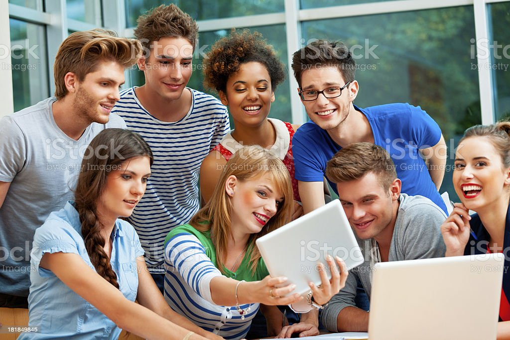 Students using a digital tablet Large group of happy university students gathering around a digital tablet and taking a self picture. 20-24 Years Stock Photo