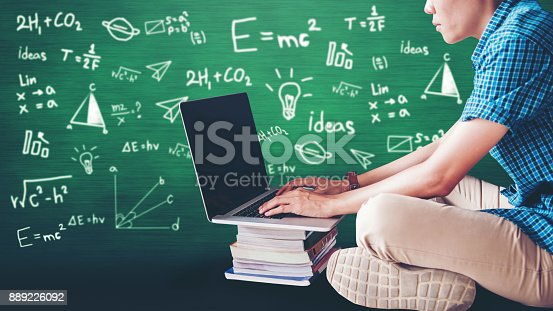 947303582 istock photo Students using laptop for research homework in college, education concept with blackboard background 889226092