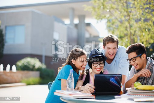 istock Students using laptop together outdoors 143071442