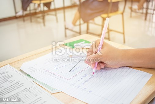 istock Students using pen writing information on white answer paper in high school, Asian exams room, Tests or examination is assessment intended to measure knowledge, skill, aptitude, Education Concept 881210052