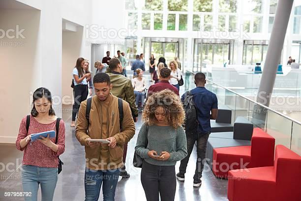 Students walk in university campus using tablets and phone picture id597958792?b=1&k=6&m=597958792&s=612x612&h=epce7p b2zzasoob3jb91 gizh69vz0gx3lq09nmss4=