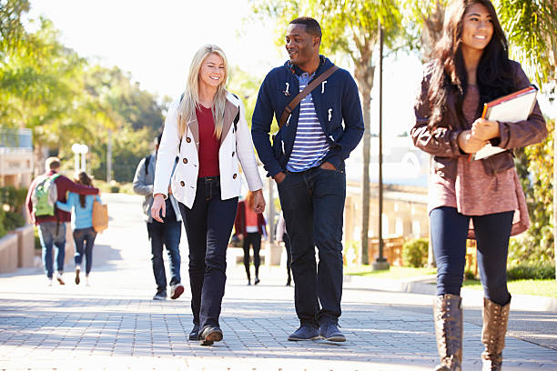 Students Walking Outdoors On University Campus stock photo