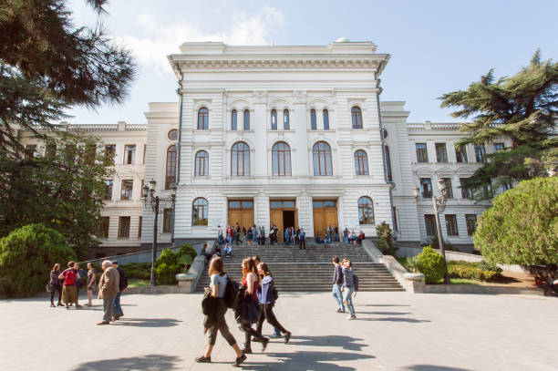 Students walking past main building of the Tbilisi State University, established 1918 stock photo