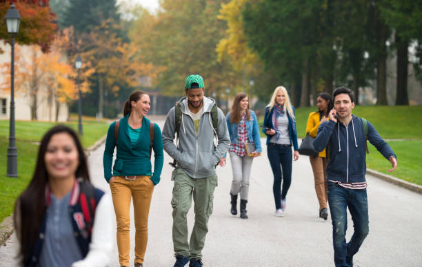 Students Walking Through The Park - foto stock