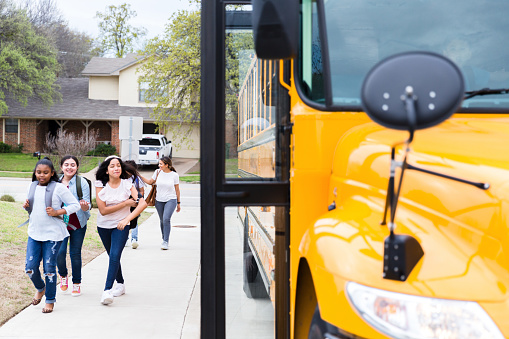 A group of students walk to a school bus at a bus stop in their neighborhood.