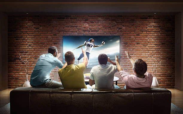 students watching american football game at home - 注視する ストックフォトと画像