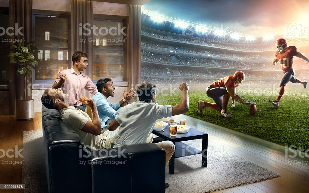 Students watching very realistic American football game at home - Photo
