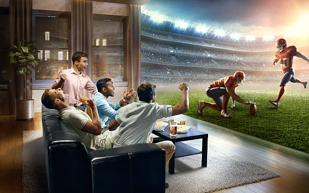 Students watching very realistic American football game at home stock photo
