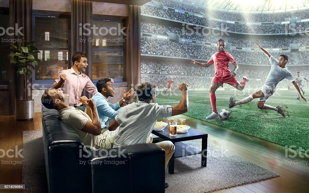 Students watching very realistic Soccer game on TV stock photo