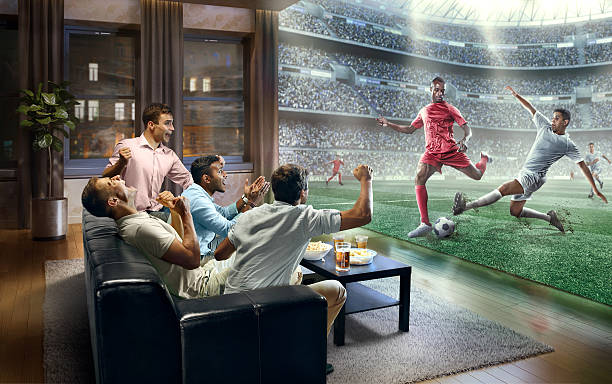 Students watching very realistic Soccer game on TV - foto de acervo