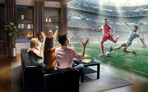 Students watching very realistic Soccer game on TV - Photo