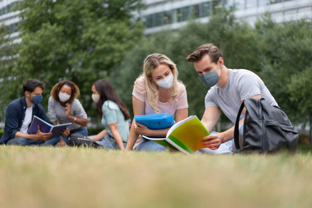 Students wearing a facemask while studying outdoors stock photo