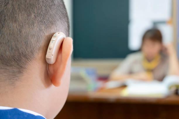 estudantes que usam próteses auditivas para aumentar a eficiência auditiva. - surdo - fotografias e filmes do acervo