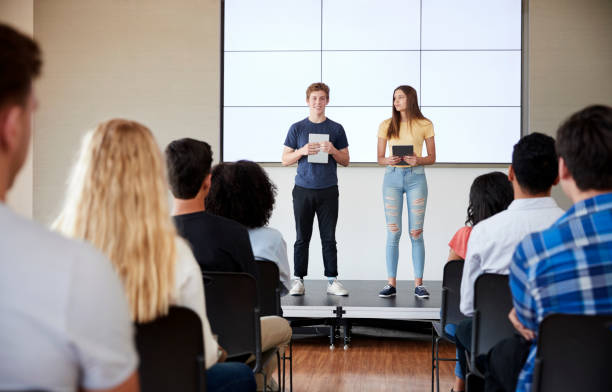Students With Digital Tablets Giving Presentation To High School Class In Front Of Screen stock photo