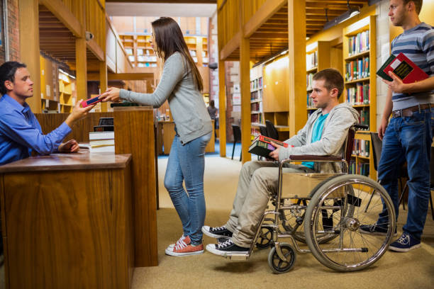 students with handicapped man in row at library counter - banchi scuola foto e immagini stock
