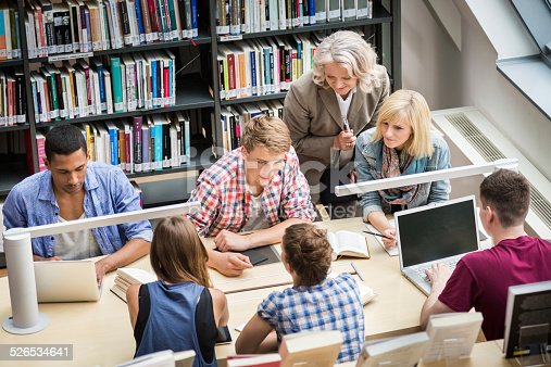 877026364 istock photo Students With Teacher Learning In Library 526534641