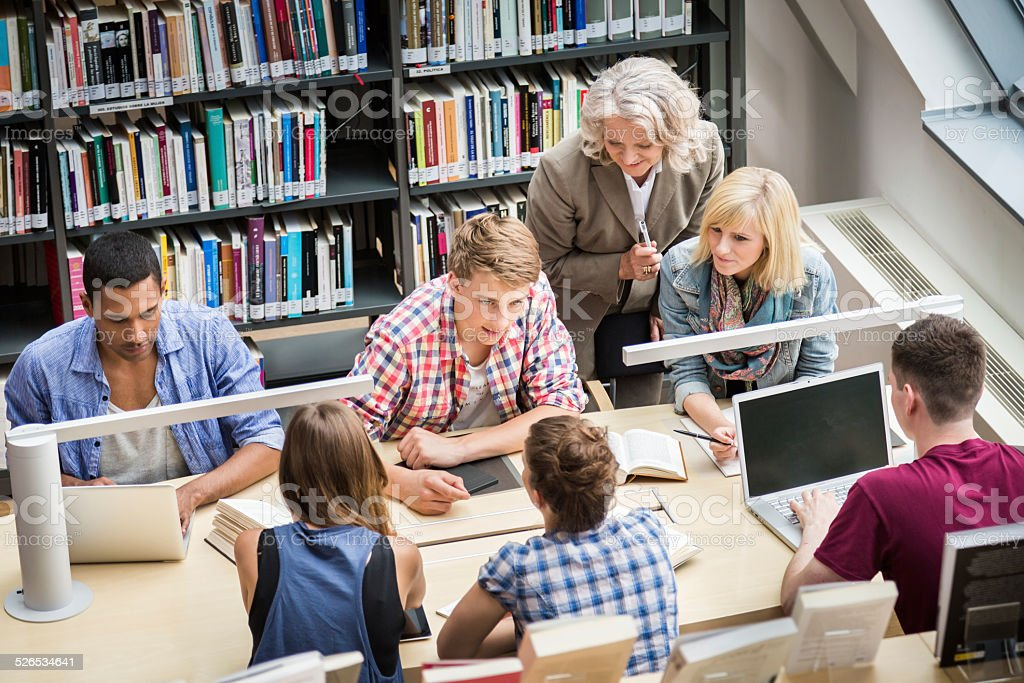 Students With Teacher Learning In Library stock photo